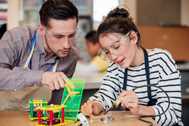 Supporting a Student Male teacher helping student with construction in STEM lesson. soldering iron stock pictures, royalty-free photos & images
