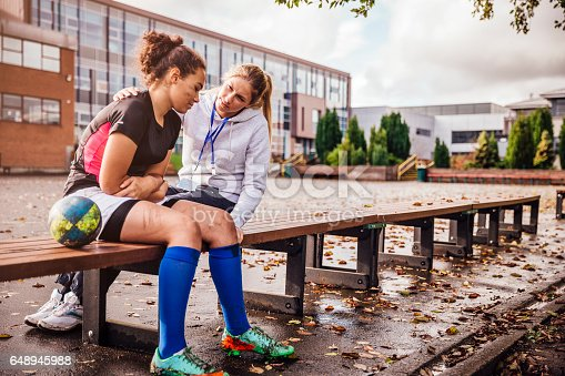 Teenage girl sitting on a bench with her rugby ball at one side. Dirty with mud after her match. Female coach sits close supporting her as the girl looks sad.