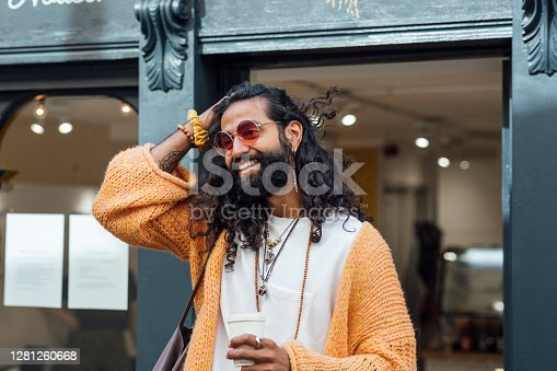 A shot of a mid adult Pakistani hipster man walking out of a local coffee shop with an eco friendly, biodegradable paper takeaway cup. He is wearing casual bohemian clothing, accessories and is tinted sunglasses.