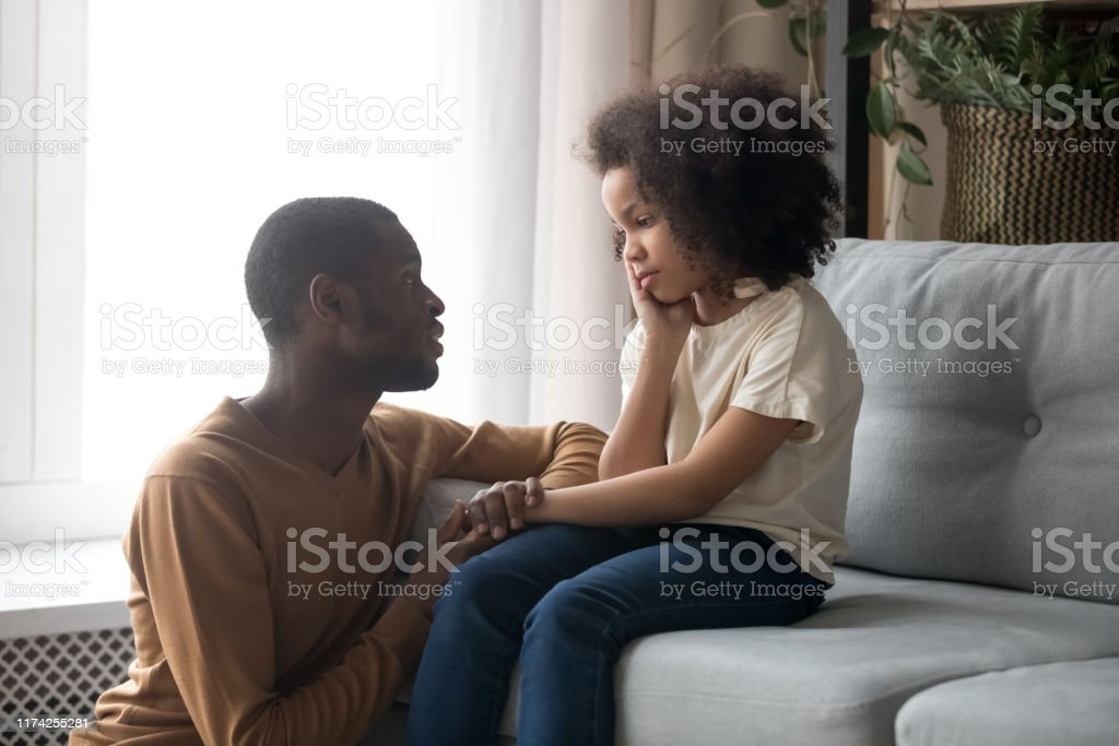 Supportive black dad talk cheering sad preschooler daughter Loving african American father talk with upset preschooler daughter helping with problem, caring black young dad speak with sad girl child holding caressing hand, show support and understanding African Ethnicity Stock Photo