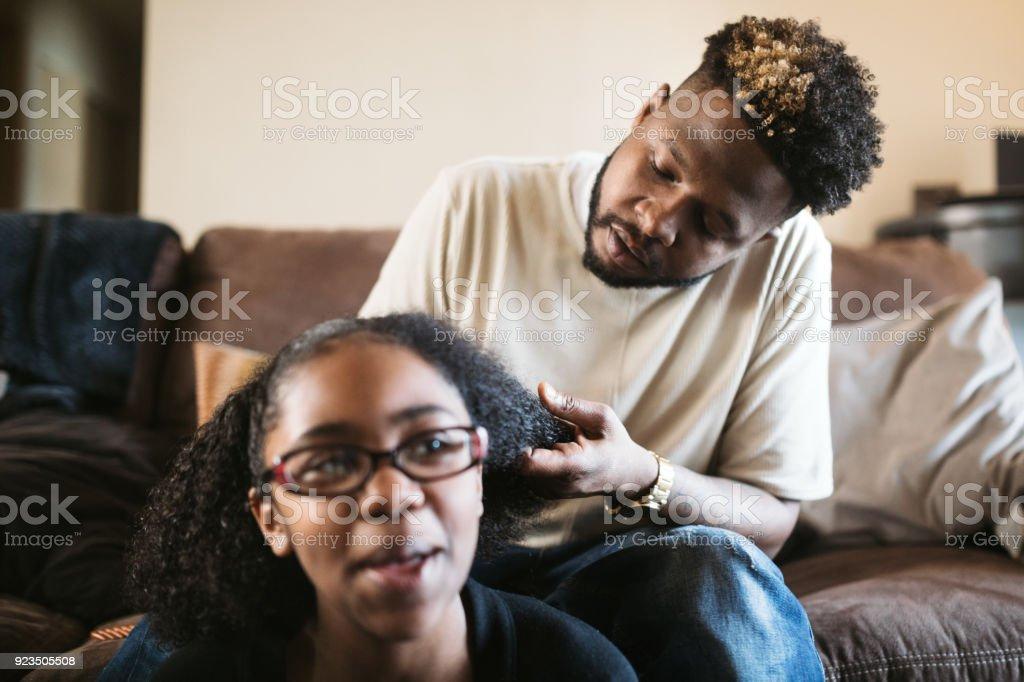 Padre solidario ayuda a hija trenza de pelo - foto de stock