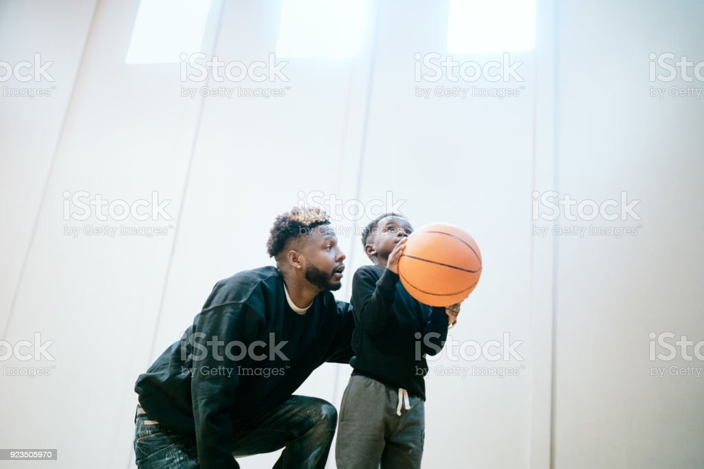 Supportive Father Plays Basketball with Son stock photo
