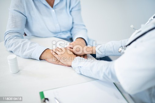 667827758 istock photo Supportive female doctor and senior woman holding hands. 1180819418