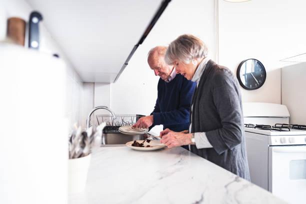 unterstützende ehemann seine frau in der küche zu helfen - seniorenwohnungen stock-fotos und bilder