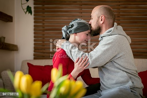 469949126 istock photo Supportive husband kissing his wife, cancer patient, after treatment in hospital. Cancer and family support concept. 941733116