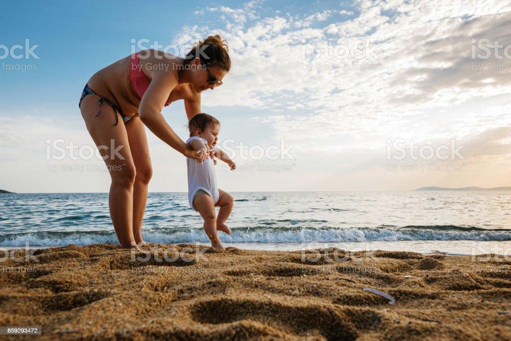 Unterstützende Mutter hilft ihrem Baby zu gehen Lizenzfreies stock-foto