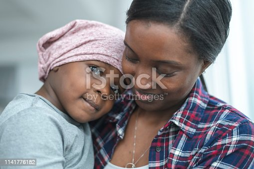 637119208 istock photo Supportive mother holds child with cancer 1141776182