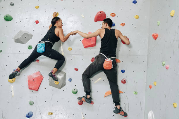 parede de escalada de desportistas de apoio acima - escalação em rocha - fotografias e filmes do acervo