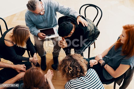 istock Supportive therapist comforting a young man who lost his parents in group therapy for people in mourning 1002736140