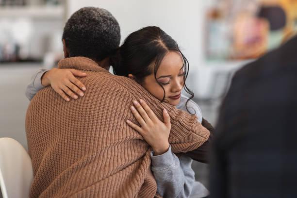 le donne di supporto si abbracciano mentre partecipano a una sessione di terapia di gruppo - assuefazione foto e immagini stock