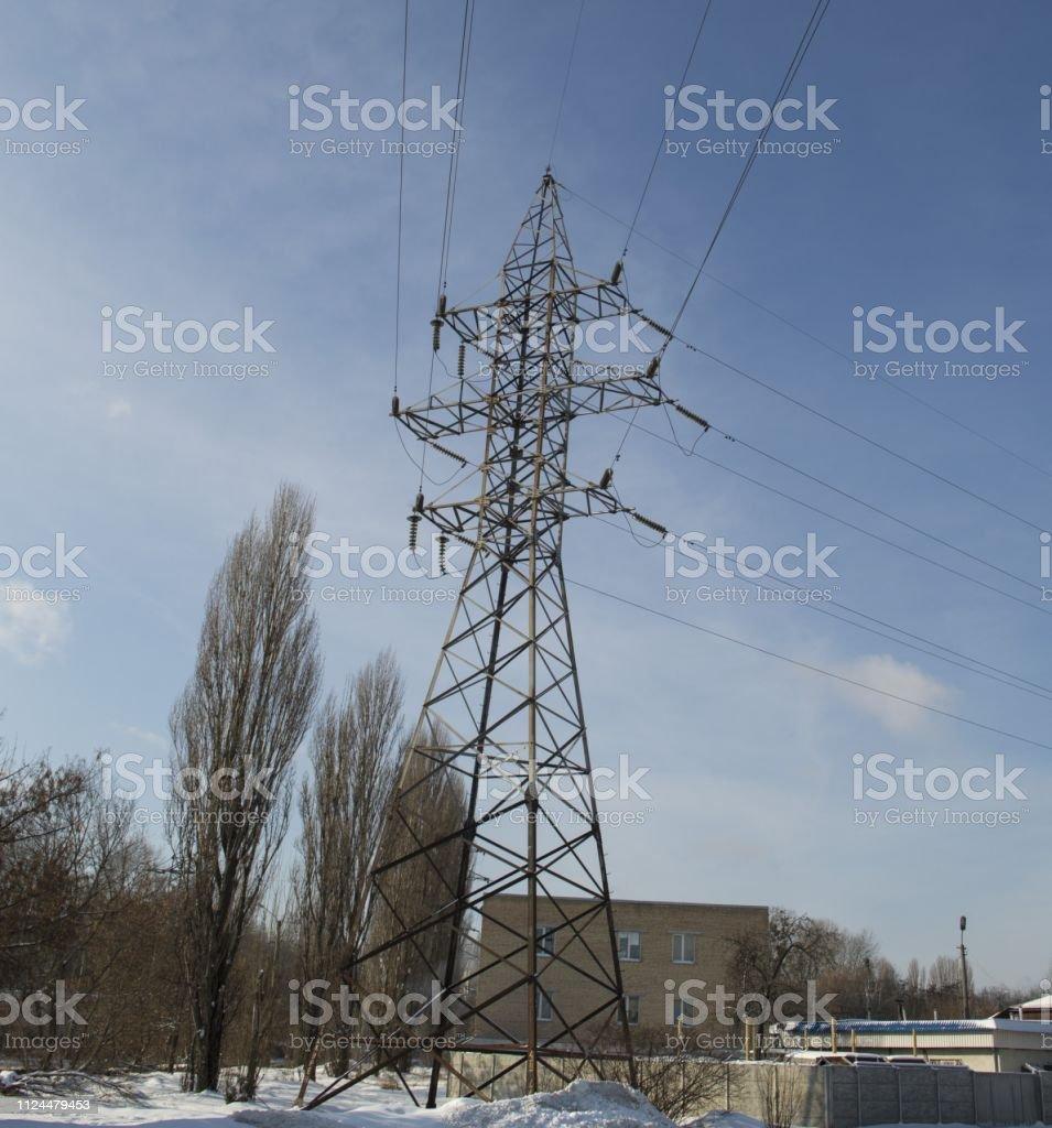 High-voltage transmission line pylons against a blue sky on a sunny...
