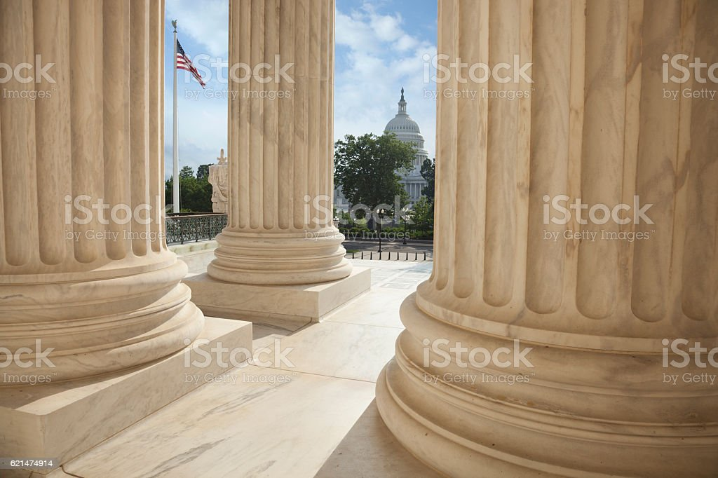 Supreme Court columns with American flag and US Capitol stock photo
