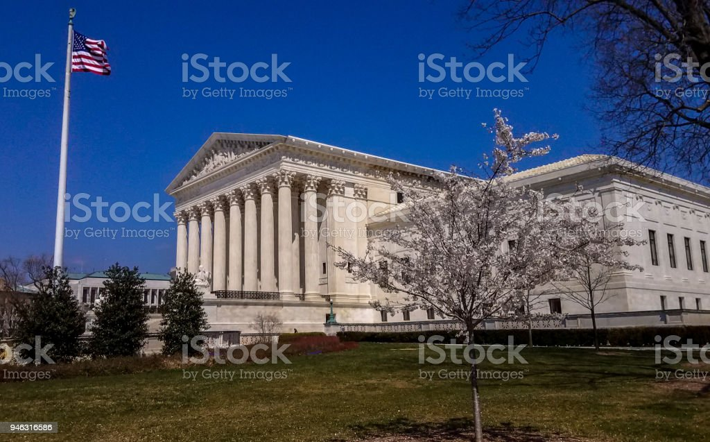 Supreme Court of the United States and American Flag in Washington, DC stock photo