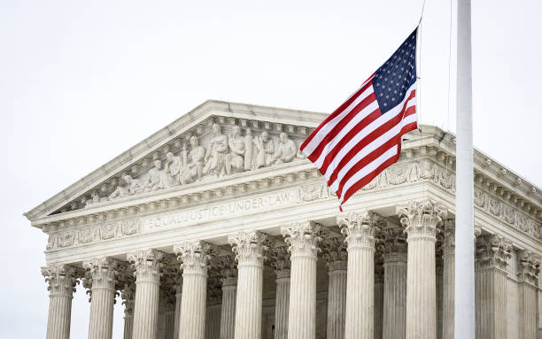 """Supreme Court A picture of the supreme court, with the US flag waving in front of the phrase """"Equal Justice Under Law"""" us supreme court building stock pictures, royalty-free photos & images"""