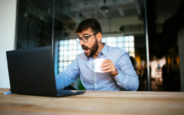Suprised businessman indoors Photo of a young businessman with suprised face shocked computer stock pictures, royalty-free photos & images
