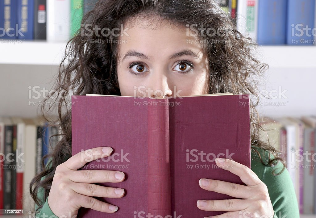 suprised girl is hidden behind a book royalty-free stock photo