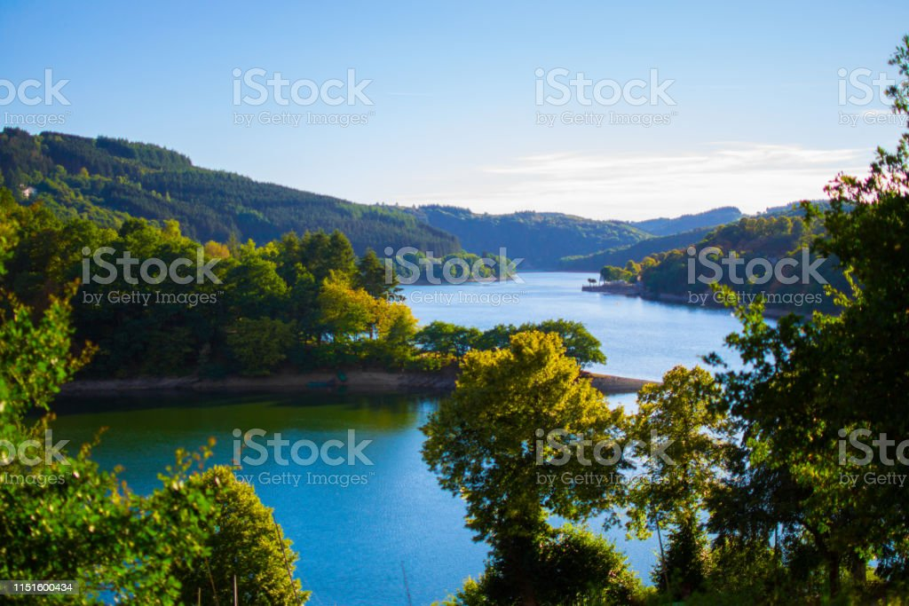 Sure river in Lultzhausen, Esch-sur-Sure, Luxembourg. Beautiful landscape with green mountains at the both sides - Royalty-free Adulation Stock Photo