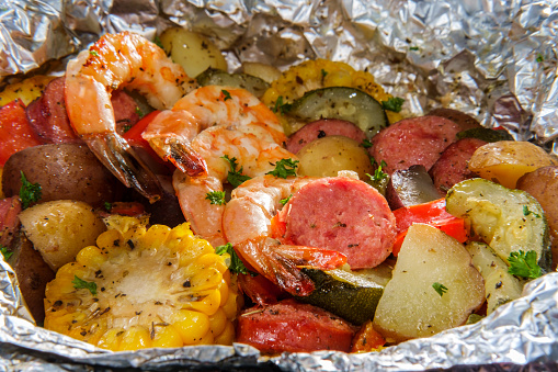 American surf and turf dinner cooked and served in tin foil packet featuring shrimp multicolored new potatoes and kielbasa sausage