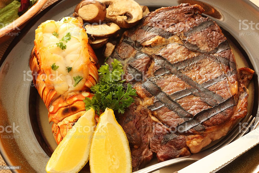 Surf and turf meal with lemon and steak stock photo