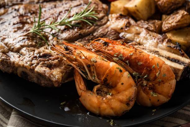 surf and turf, ribeye steak and grilled prawn stock photo
