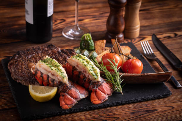 surf and turf with tomahawk rib eye steak and lobster tail stock photo