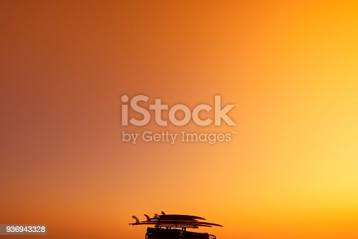 Surf boards and luggage on the roof of the van at warm summer sunset light with sky as copy space