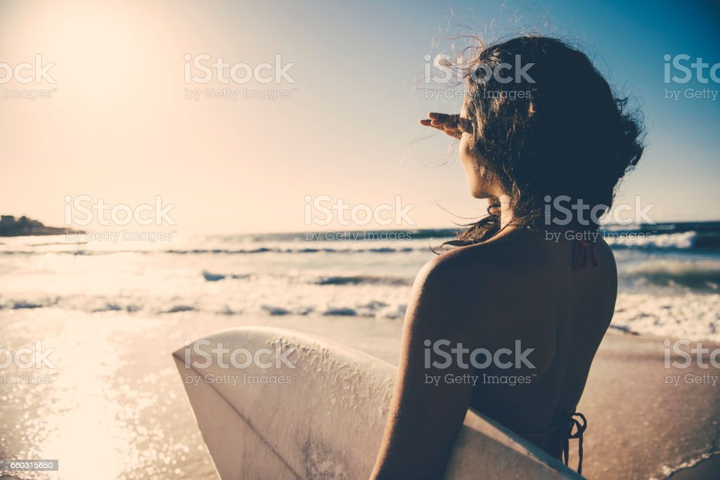 Surf girl looking into distance stock photo