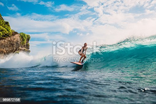 istock Surf girl on surfboard. Woman in ocean during surfing. Surfer and ocean wave 989872158