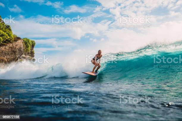 Photo of Surf girl on surfboard. Woman in ocean during surfing. Surfer and ocean wave