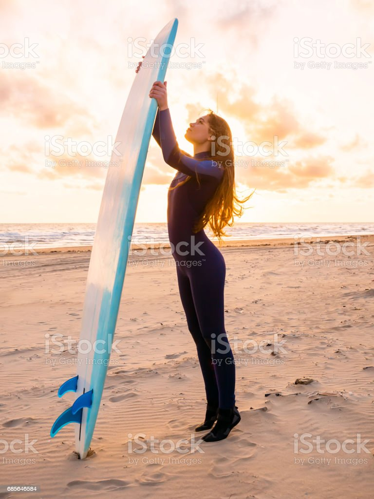 Surf girl with long hair and surfboard on a beach at sunset or sunrise. Surfer and ocean 免版稅 stock photo