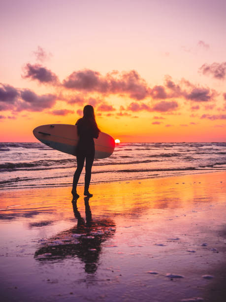 Surf girl with surfboard with warm sunset or sunrise colors stock photo