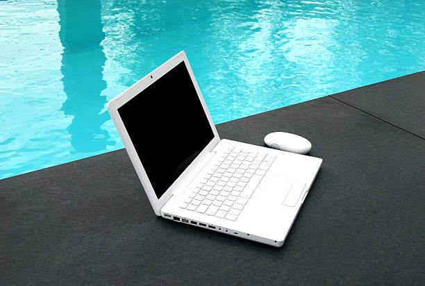 surf bright white laptop on granite beside a pool. black border stock pictures, royalty-free photos & images