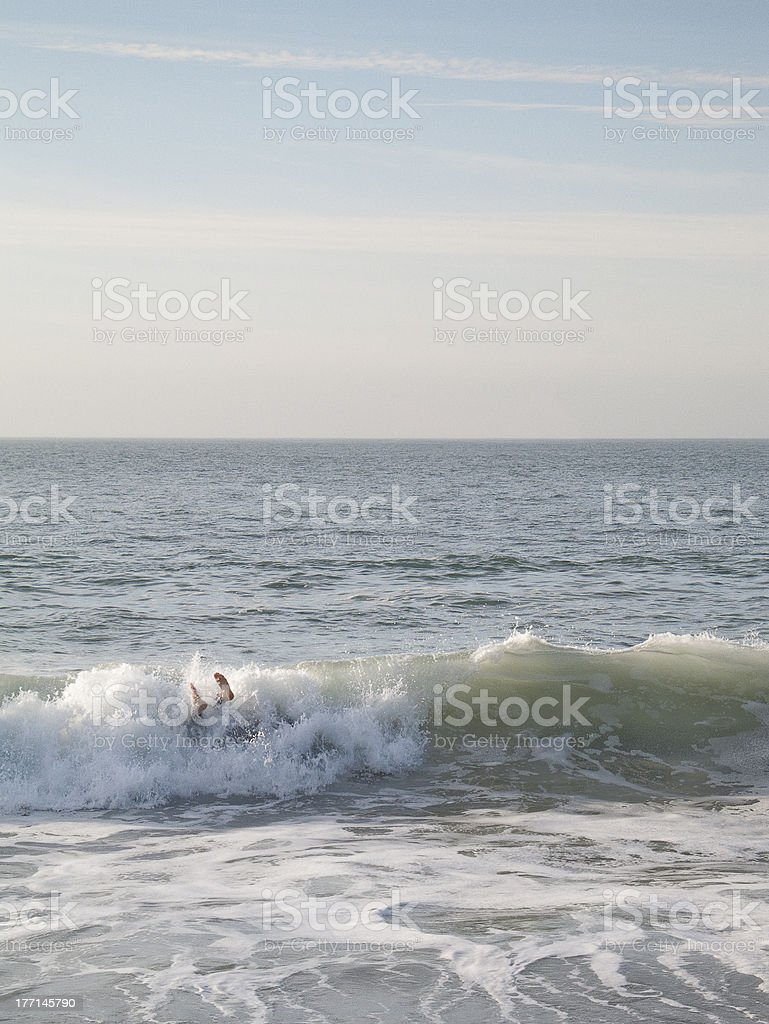Surf wave overwhelms person as feet pop out of water royalty-free stock photo