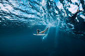 Surf woman with surfboard dive underwater with under wave.