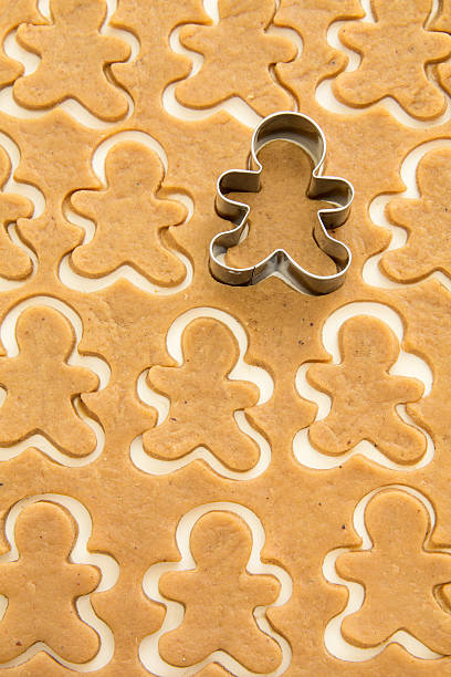 Surface full of gingerbread dough cut in man shape Gingerbread dough for Christmas cookies and cookie cutters. cookie cutter stock pictures, royalty-free photos & images