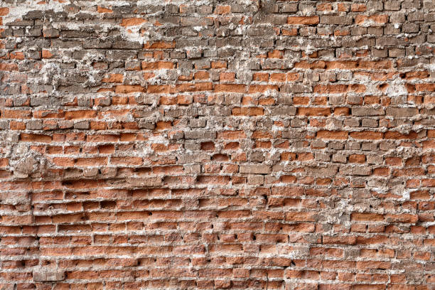 Surface of the wall is made of red crumbling brick Surface texture of an old crumbling red brick wall. devolve stock pictures, royalty-free photos & images