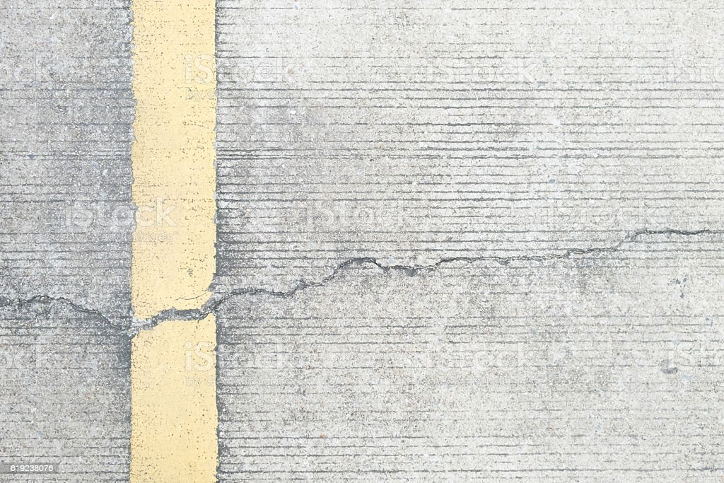 Surface of yellow line on the broken concrete street. stock photo