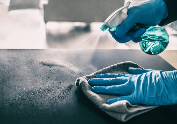 Surface sanitizing against COVID-19 outbreak. Home cleaning spraying antibacterial spray bottle disinfecting against coronavirus wearing nitrile gloves. Sanitize hospital surfaces prevention stock photo