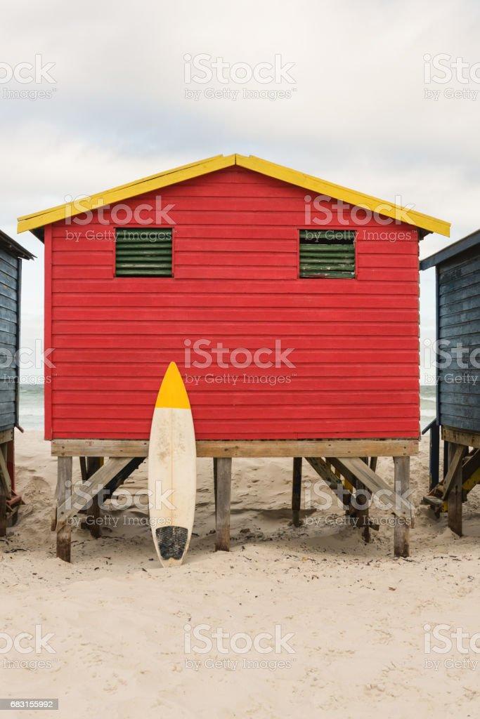 해변에서 붉은 나무 오두막으로 서핑 보드 royalty-free 스톡 사진