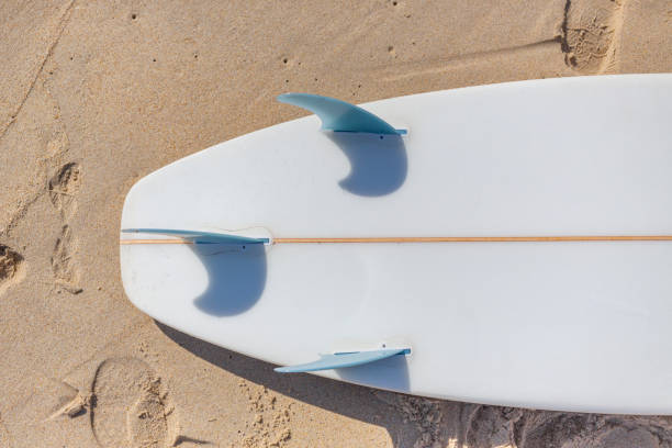 Surfboard fins and beach sand stock photo