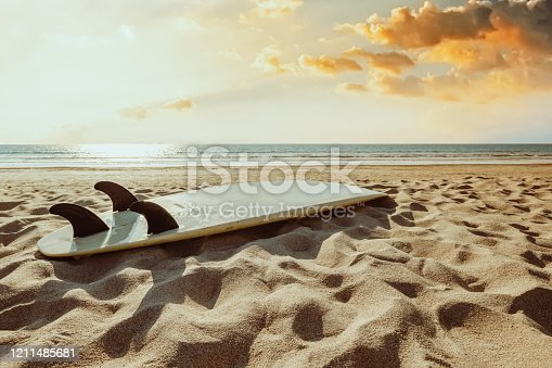 Surfboard on beach background at sunset. Travel adventure and water sport.  retro color tone effect.