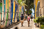 Honolulu: Tourists walk by a surfboard lined alley off the commercial shopping district of Kalakaua Avenue by Waikiki Beach.  Surfboards are locked up here when not in use.