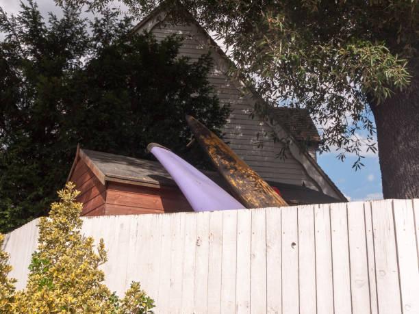 surfbrädor toppar vilar mot ett skjul bakom väggen i trädgården - surf garage bildbanksfoton och bilder
