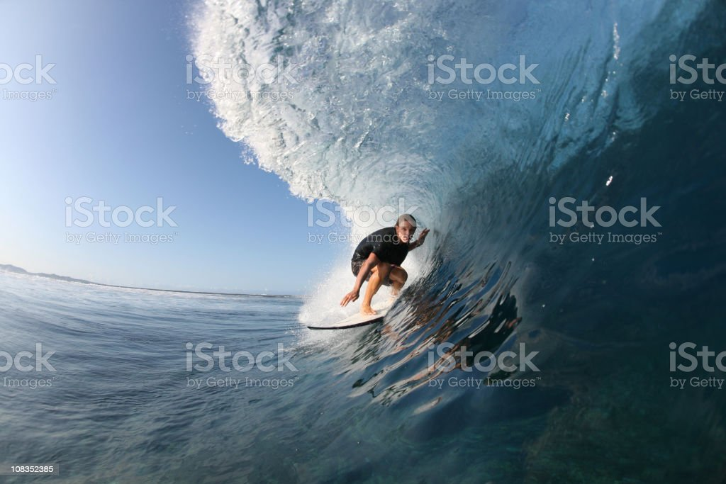 Surfer action shot catching a wave in the ocean stock photo