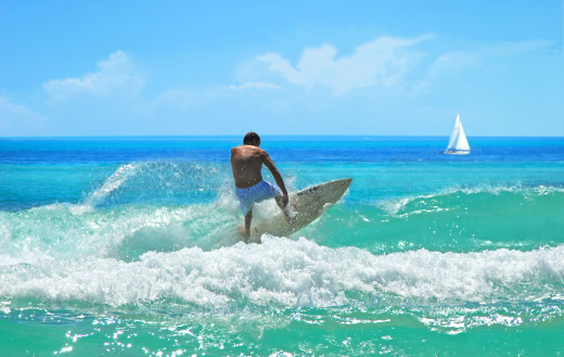 Surfer catching wave on gogeous turquoise sea with sailboat in the distance
