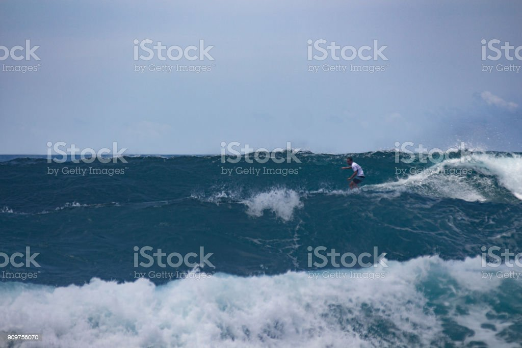 Surfer and the waves showing the power of the ocean stock photo