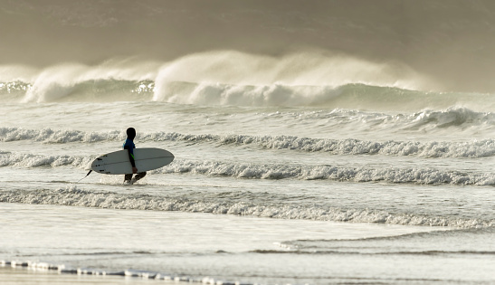 Surfer approaches Waves, Fistral Beach, Cornwall, UK