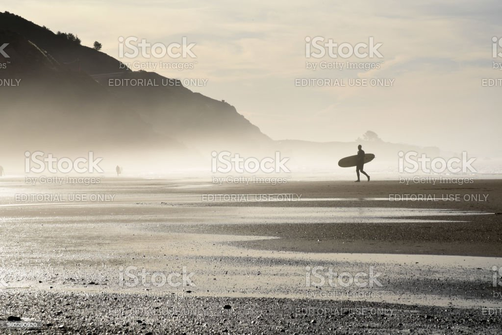 Surfer at sunrise in California stock photo