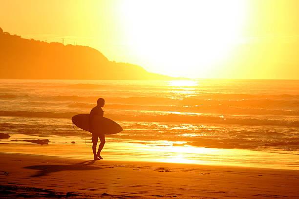 Surfista al atardecer - foto de stock