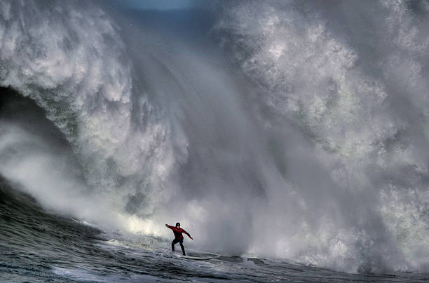 surfer at the bottom of a huge crashing wave  - stor bildbanksfoton och bilder